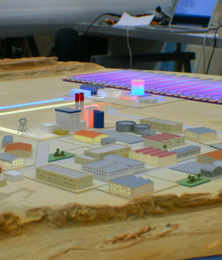 Maquette animée et lumineuse représentant plusieurs bâtiments.
